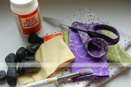 Supplies Needed: mod podge, small rocks, fabric, scissors and paint brush.